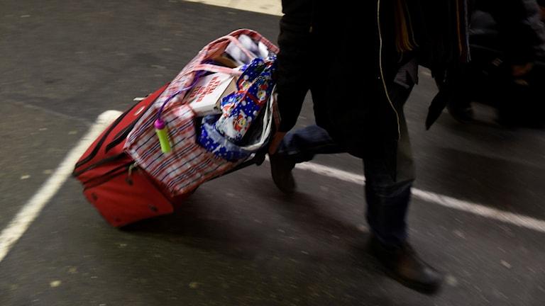 En person som drar en ullväska och påse med julklappar.