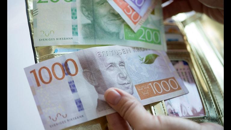 Bilden visar sedlar som sticker ut ur en plånbok.