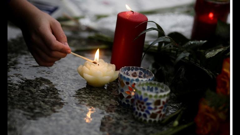 En kvinna tänder ljus för offren för terrorattacken i Paris.