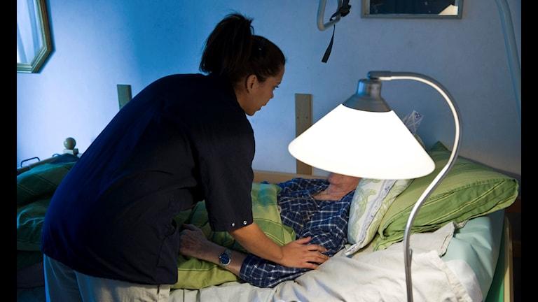 Vårdpersonal hjälper en äldre människa som ligger till sängs.