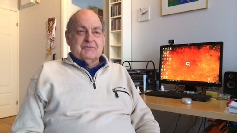 En man i en vit tröja framför datorn