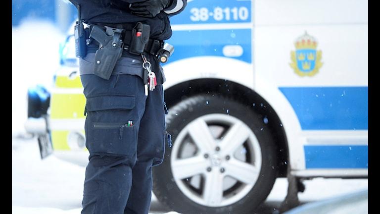Bilden visar en polis' ben och en polisbil.