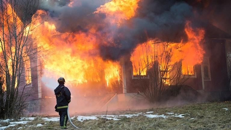Bilden visar en brandman som släcker en brand.