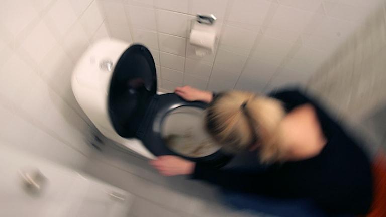 Magsjuk kvinna på toaletten