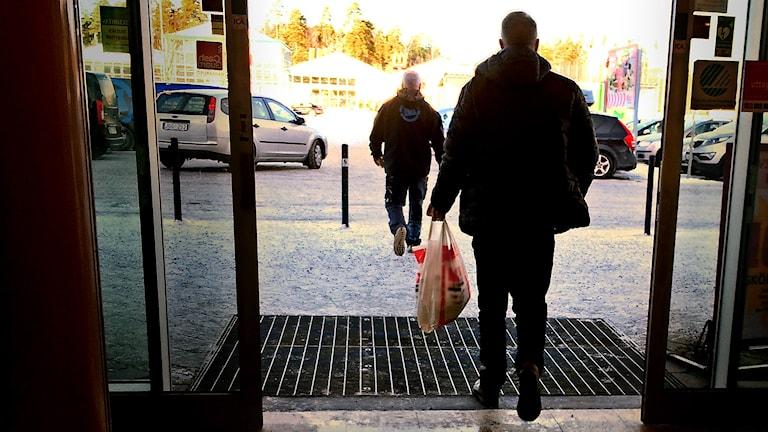 Bilden visar kunder på väg ut ur en butik efter att ha handlat.