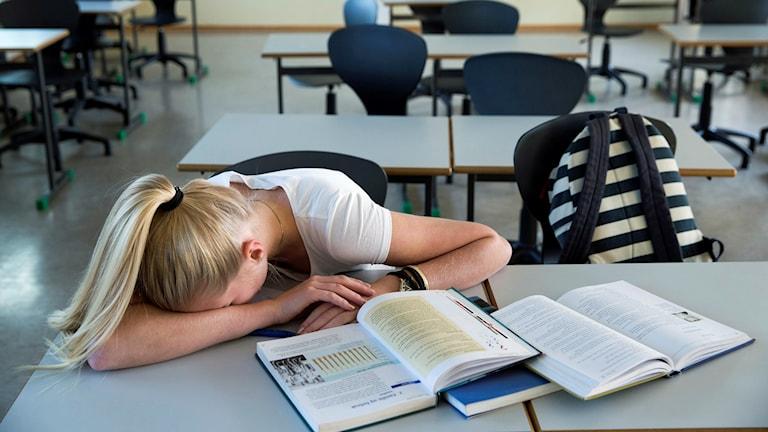 Bilden visar en elev som gömmer ansiktet i armvecket.