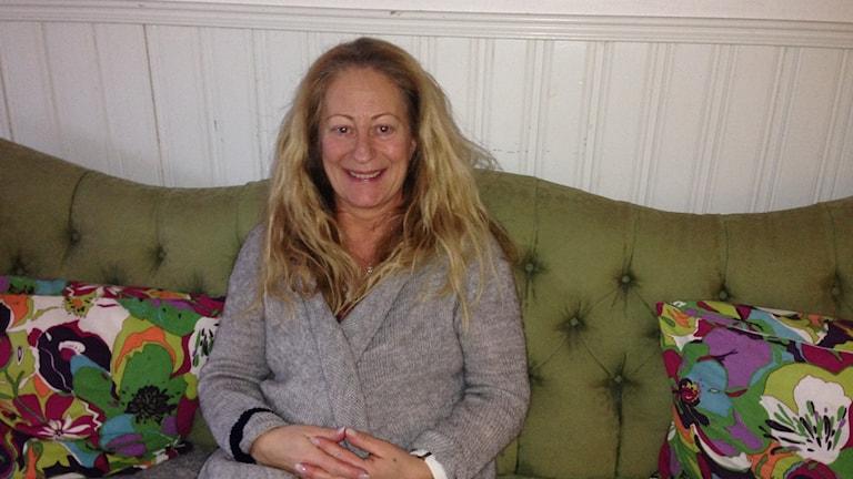 Catarina Anelius sitter i en grön soffa på boendet i Falun.