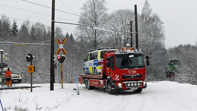 Bilden visar bärgning av polisbilen som fastnat på tågrälsen när bommarna gått ned.