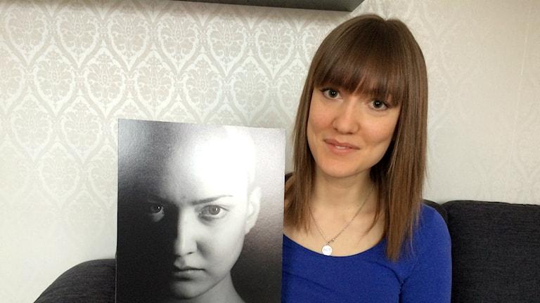 Emma Skoglund håller upp en bild på sig själv från tidigare.