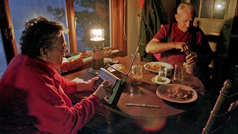 Bilden visar en man och en kvinna som sitter vid ett köksbord och bland annat lyssnar på batteridriven radio.