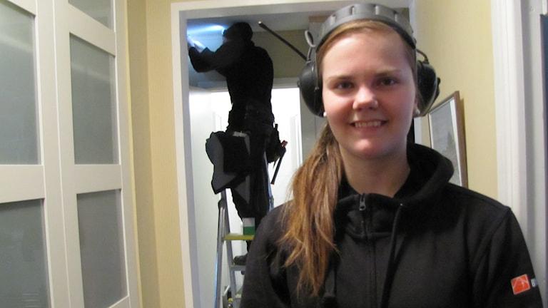 Paulina Johansson tittar in i kameran och ler. Hon har på sig en svart tröja och har ett par svarta hörselskydd på huvudet. Hon har långt brunt hår i en tofs. Foto: Annelie Hüllert-Storm/Sveriges Radio