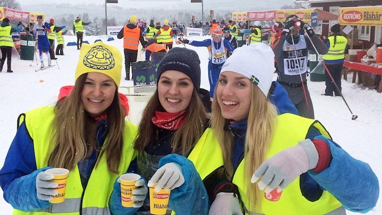 Sara Olsson, Maja Böckman och Evelina Melkersdotter langar blåbärssoppa och sjunger vackert för Vasaloppsåkarna som passerar kontrollen i Oxberg.