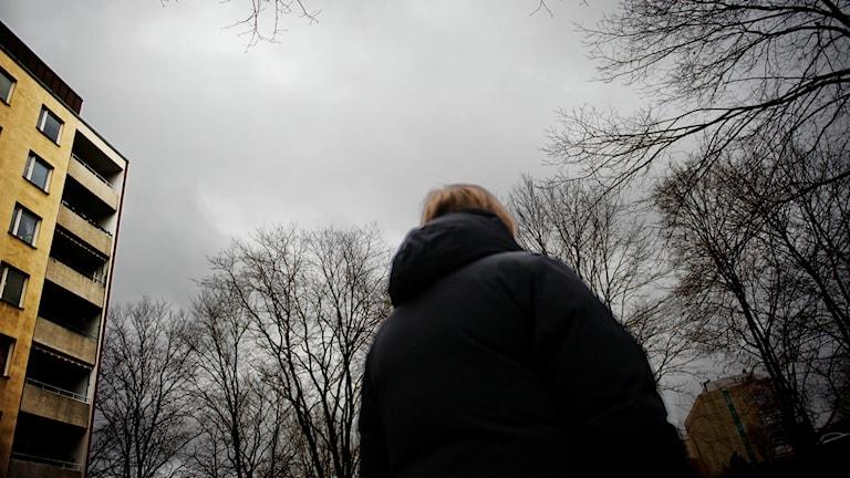 En kvinna i täckjack med ryggen mot kameran.