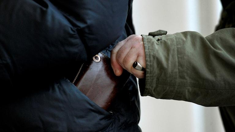 Bilden visar en person som tar en plånbok ur en jackficka.