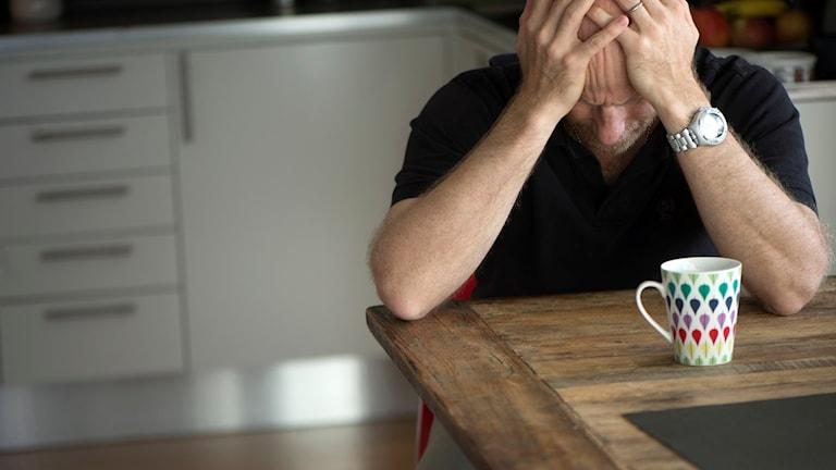 En man sitter vid köksbordet med ansiktet i händerna
