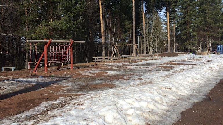 En bild av skolgården på Nyhedsskolan i Rättvik. Det är en röd klätterställning med nät och pålar, och en inhängnad gungställning. Foto: Annelie Hüllert-Storm