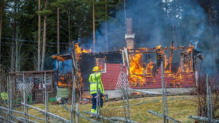 Bilden visar en brandman och ett brinnande hus.