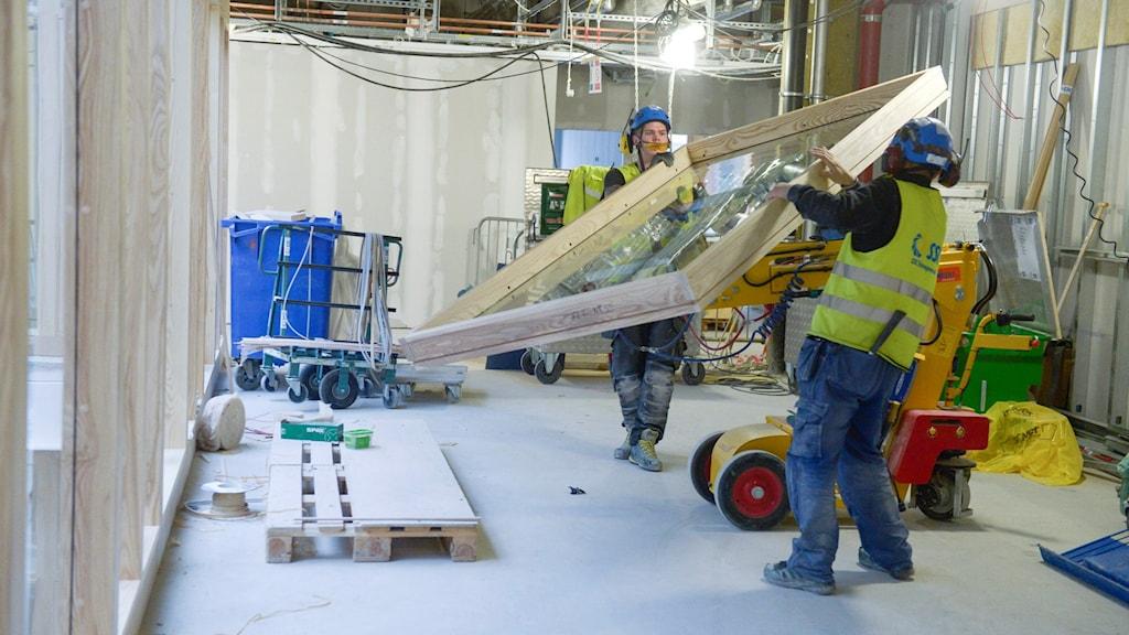 Byggarbetare bär ett fönster