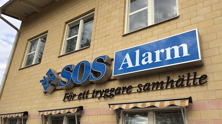 Bilden visar SOS Alarms logotype på en husvägg.