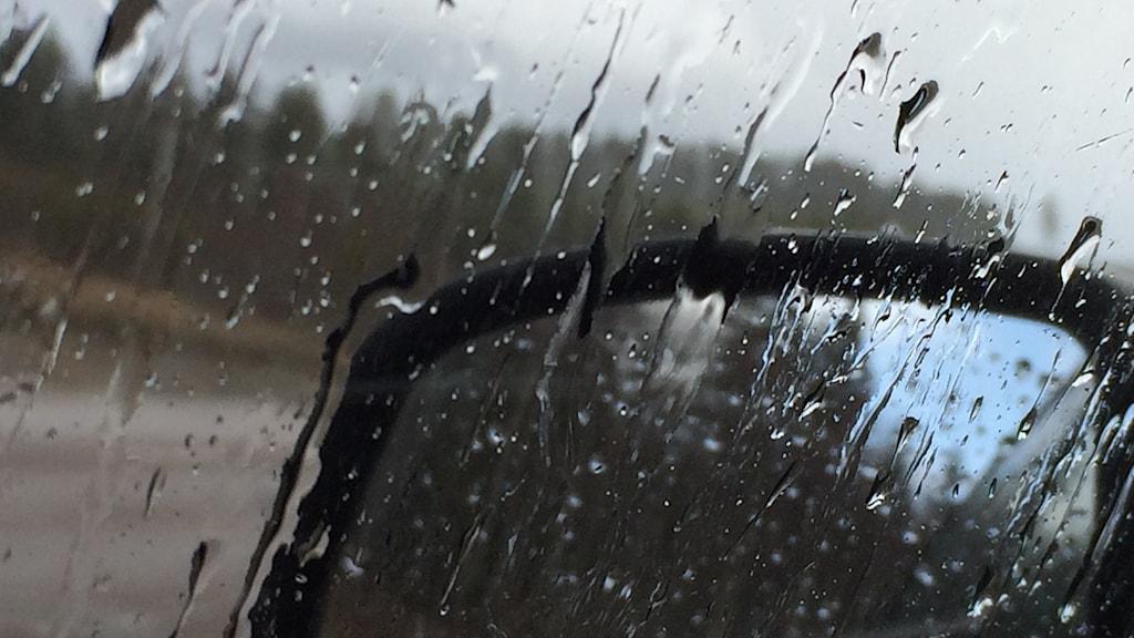 Bilden visar regndroppar på en bilruta, sett inifrån bilen.