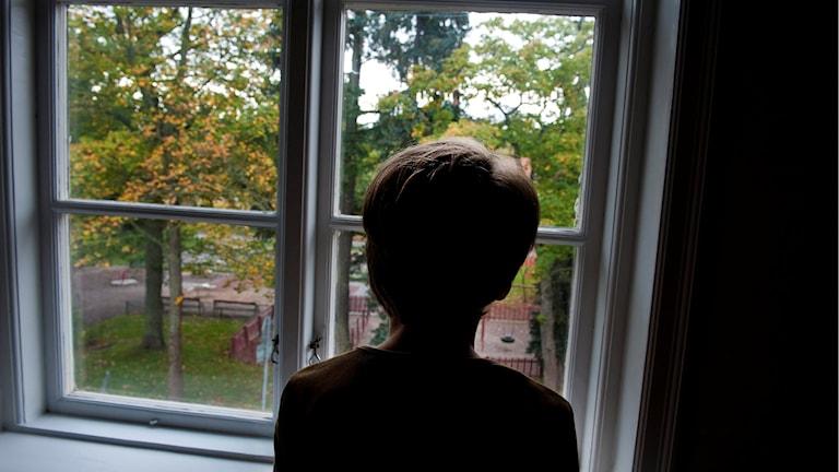 Bilden visar nacke och rygg på ett barn som tittar ut genom ett fönster.