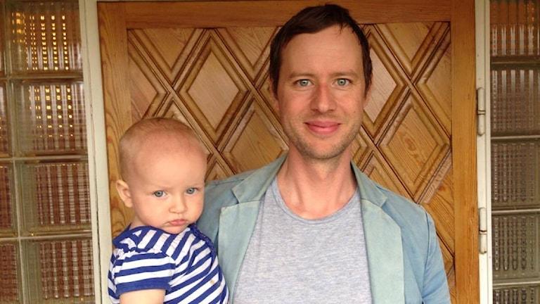 Jon Karlsson och hans bebis framför deras hus i Sundborn.
