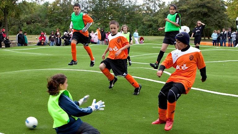 Bilden visar barn somspelar fotboll.