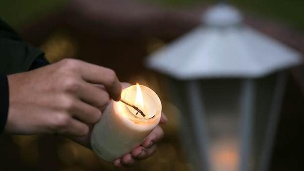 En person som tänder ett ljus på en kyrkogård