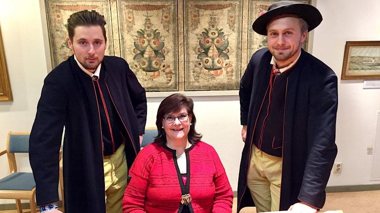 Patrik Hagman och Nils Lohman står iförda Rättviksdräkter på var sin sida av Berit Zetterqvist som sitter ner iförd en röd tröja. I bakgrunden tavlor med kurbits.