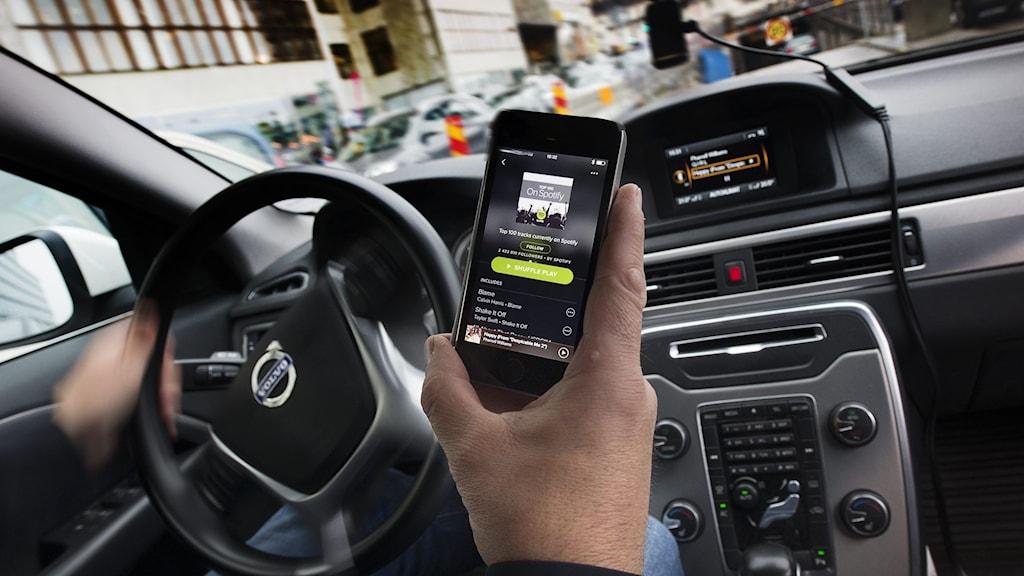 Person väljer musik på sin smarttelefon i en bil.