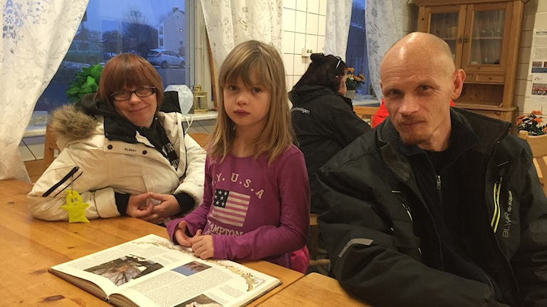 En kvinna, ett barn och en man vid ett bord inomhus.