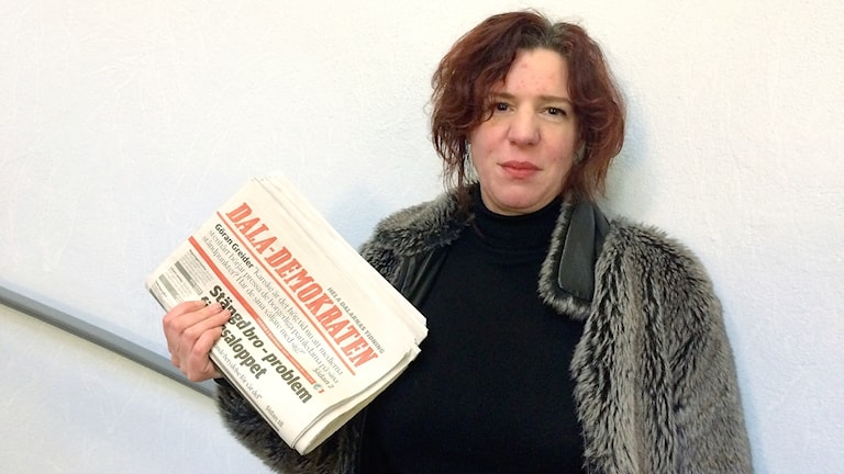 Lisa Pehrsdotter håller i en trave Dala-Demokraten-tidningar.