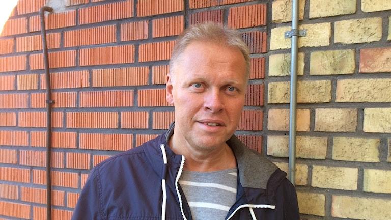 Fotot visar en man i kort blont hår i en blå jacka mot en husvägg.