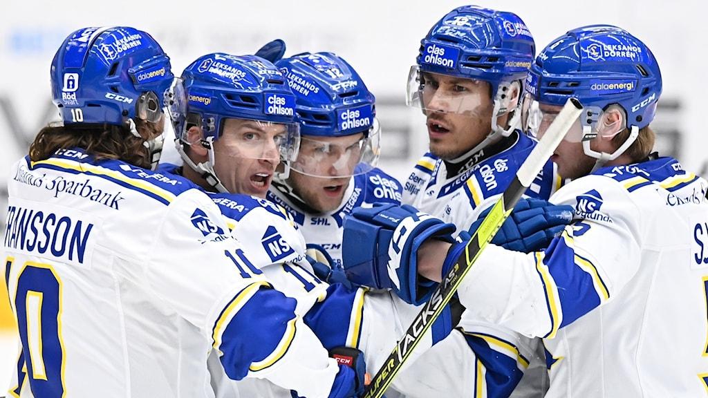 Fem hockeygrabbar med blå hjälm och vita tröjor står tätt mot varandra.
