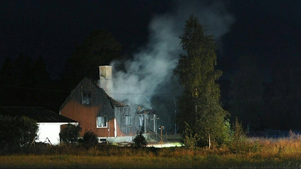 Brandrök stiger upp från en röd villa. Bilden tagen nattetid.