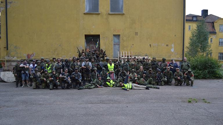 Ett gäng militärklädda människor står uppställda för fotografering framför en gul vägg.