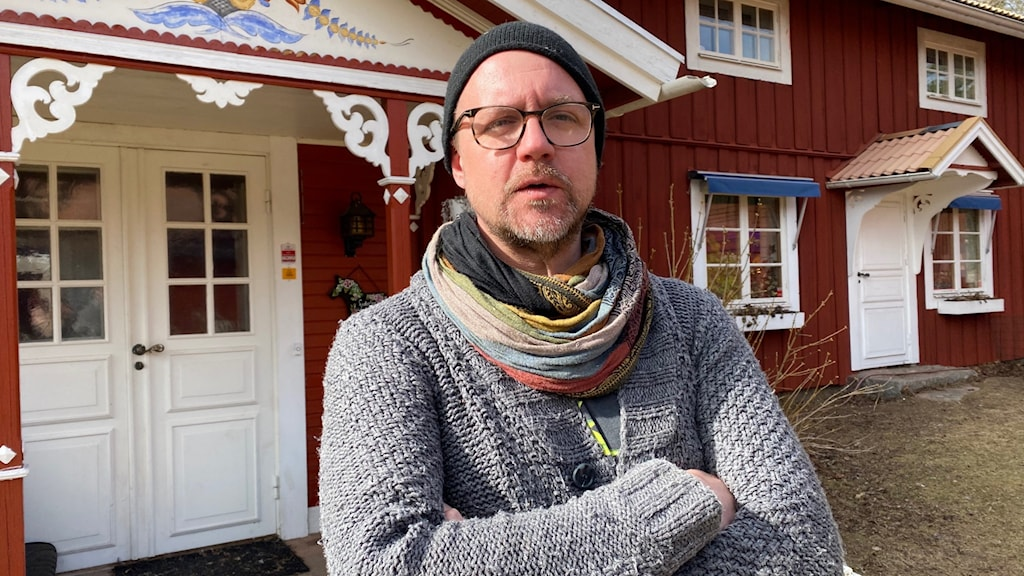 En man i grå tröja, halsduk och mössa står med armarna i kors framför ett rött trähus med en vit dörr.