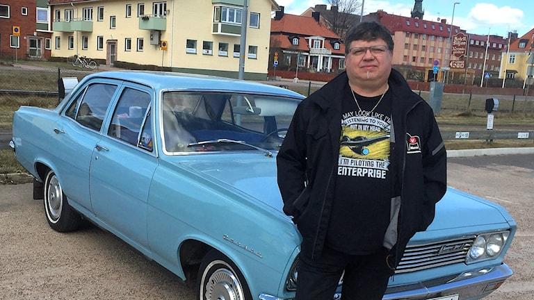 Wn man i svarta klöäder och med händerna i fickorna framför en blå bil av äldre modell.