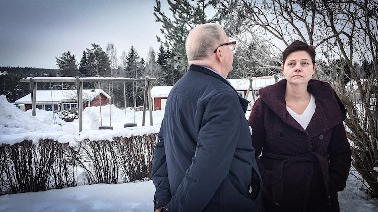 Erich och Erika står i snön utanför Erikas hus. Erich med ryggen mot kameran. I bakgrunden syns några träd och en frusen gungställning.