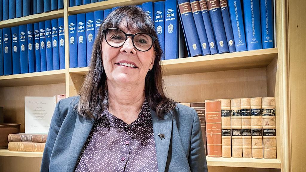 Glad medelålders kvinna med mörk lugg och glasögon, framför bokhylla