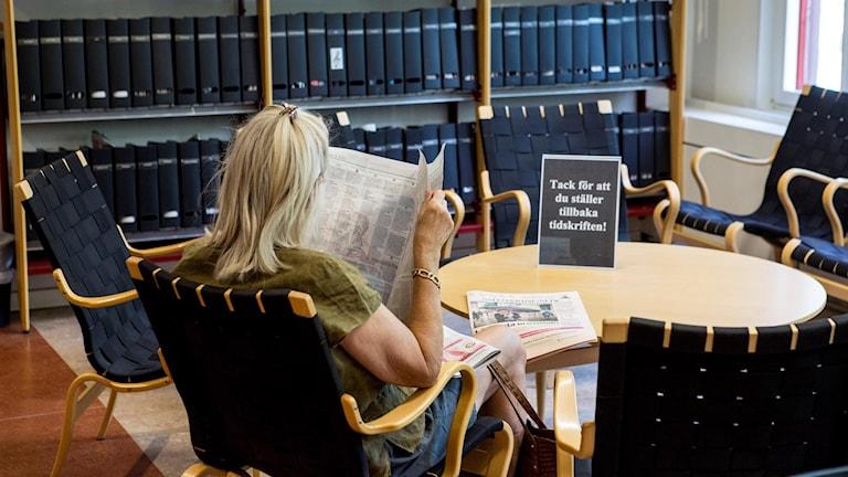 Kvinna läser tidning i bibliotek