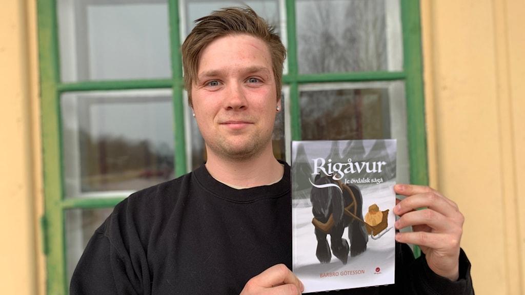 Emil Eriksson, ungdomssamordnare Älvdalens kommun, håller upp en barnbok översatt till älvdalska.