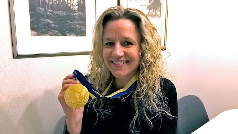 Karolina Arewång Höjsgaard håller upp en guldmedalj.