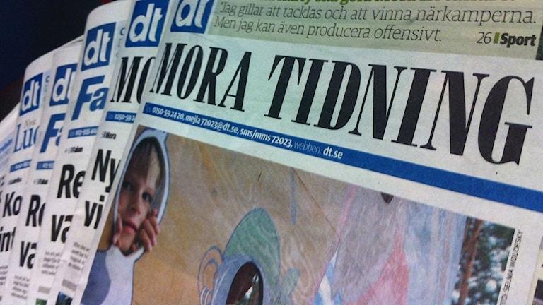 En hög med tidningar med Mora tidning längst fram.