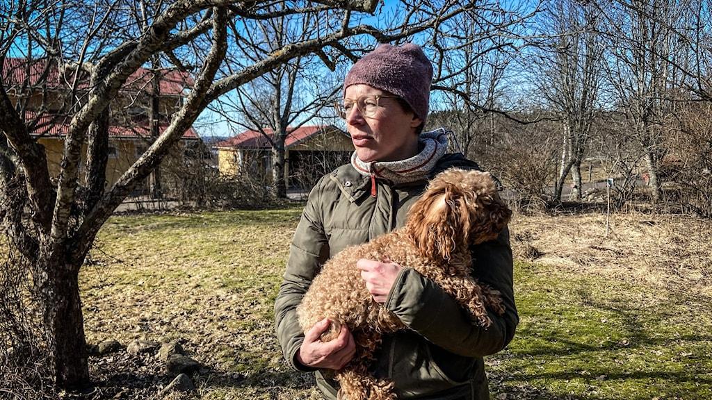 Kvinna med en hund i famnen.