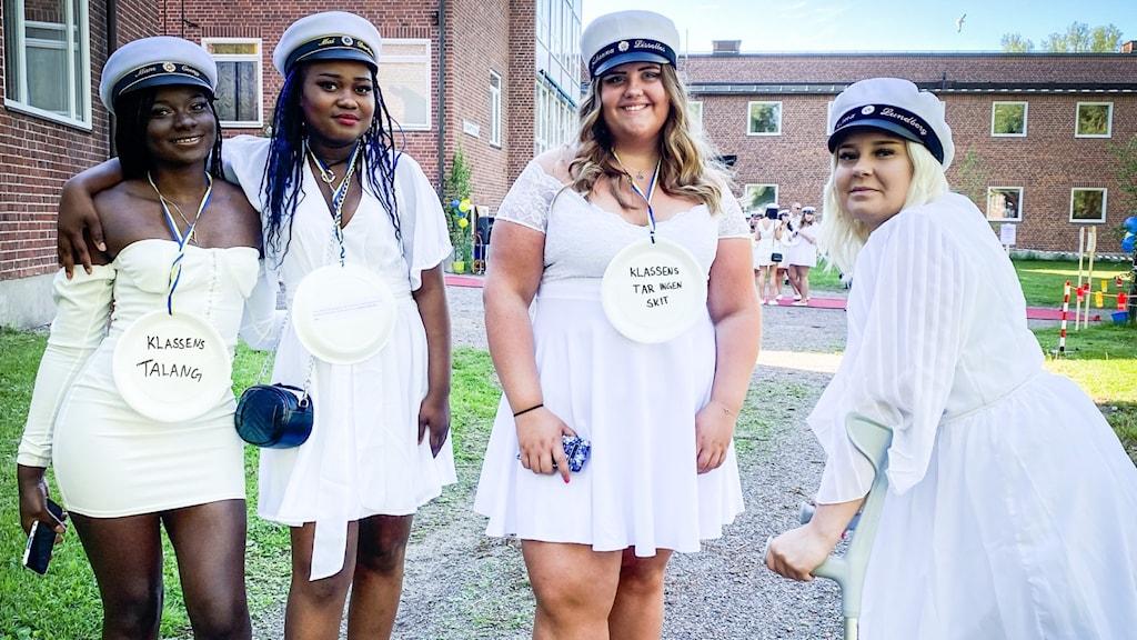 Fyra tjejer i studentmössor och vita klänningar.