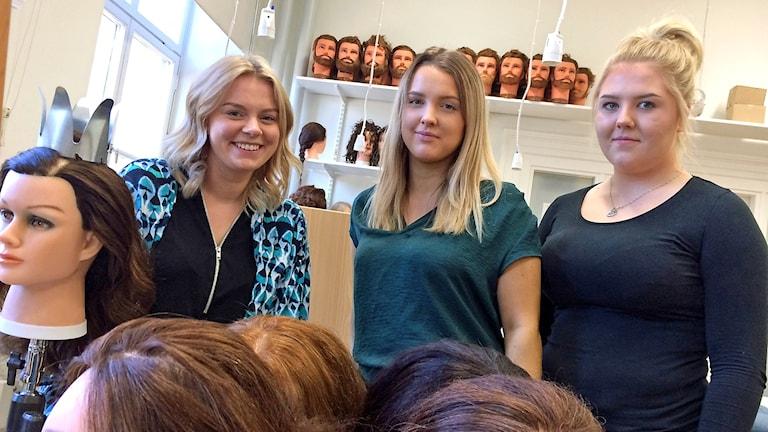 Tre tjejer bakom perukdockor.