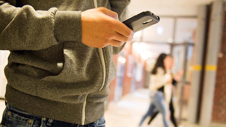 En elev i en skolkorridor som tittar på sin mobil.
