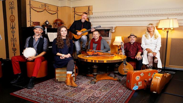 Musikerna i jul i folkton sitter tillsammans runt ett soffbord