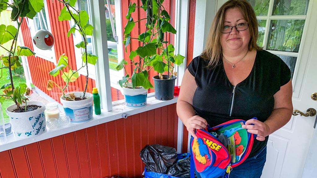 En kvinna med glasögon står och håller upp en liten barnryggsäck.